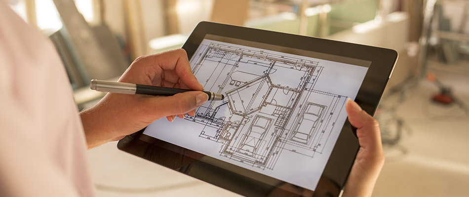 person marking up blueprints on tablet